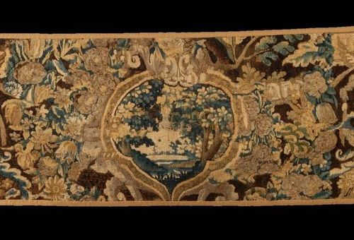 Fragment of a wool and silk tapestry with greenery and cherubs. Seventeenth cent…