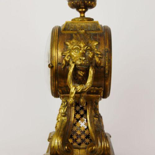 Pendule à poser en bronze ciselé et doré, reposant sur quatre volutes et flanqué…