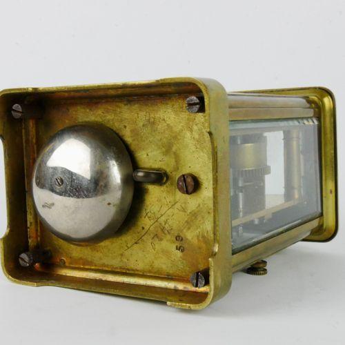 Pendulette de voyage en laiton verni formant réveil, le cadran émaillé blanc à c…