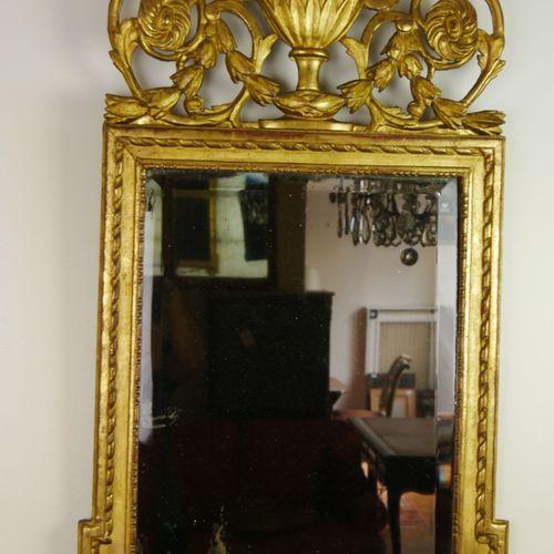 Glace rectangulaire et son fronton en bois sculpté et doré à décor ajouré de rin…