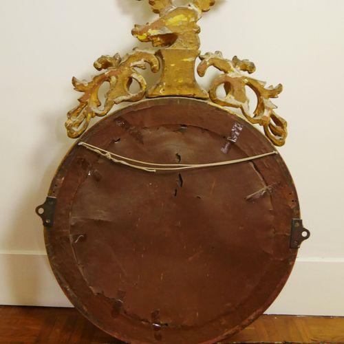 Miroir de sorcière, l'encadrement en bois et stuc doré sommé d'un aigle aux aile…