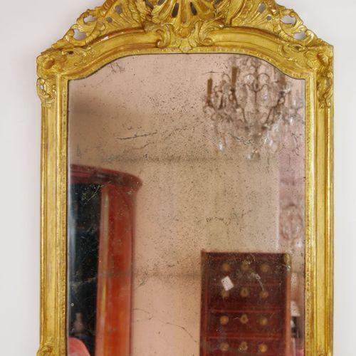 Glace en bois sculpté et doré, l'encadrement à décor d'une coquille ajourée sur …