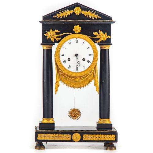 Pendule portique en marbre noir et ornementation de bronze doré. Le cadran suspe…