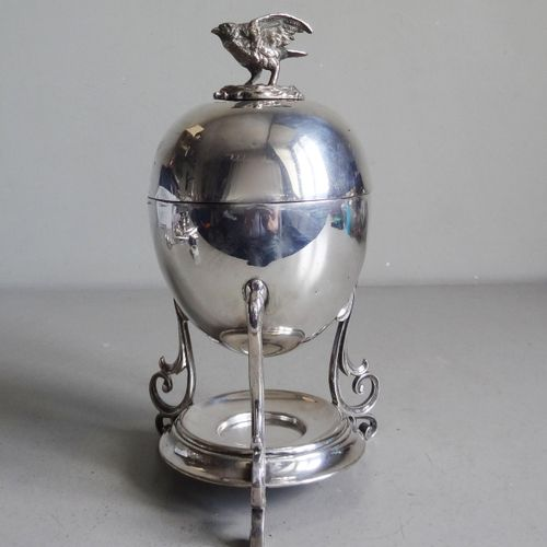 Egg shaped covered cup in silver plated metal topped by a bird on its nest. It r…