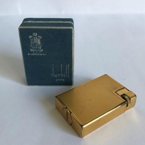 DUNHILL DUNHILL Paris  Briquet en métal doré guilloché.  Dans sa boite