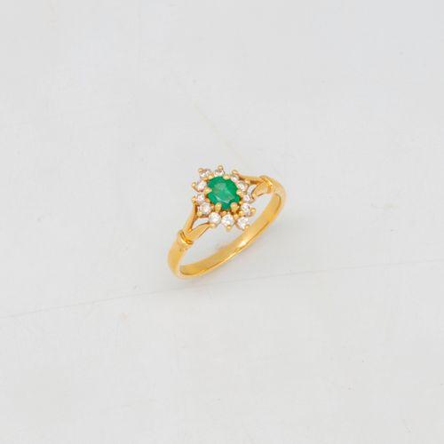 Bague en or jaune ornée d'une émeraude entourée de diamants  Poids brut : 2,75 g…