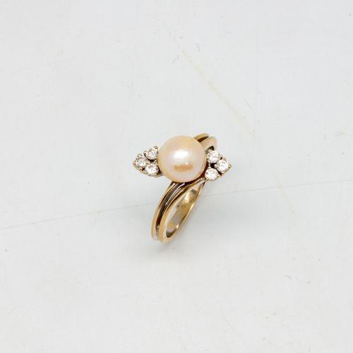 Bague en or gris ornée d'une perle de culture épaulée d'un petit motif en diaman…