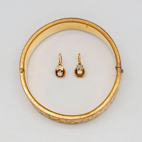 Bracelet jonc en métal doré à décor de rinceaux  On joint une paire de dormeuse …