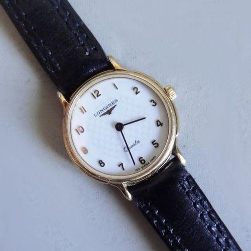 LONGINES Petite montre de Dame à cadran rond en métal doré et acier. Chiffes ara…