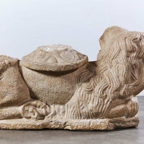 Carved marble stone lion with column. The lion is lying down, with its hindquart…