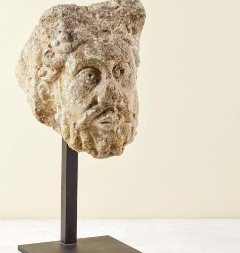 Carved stone modillon representing a bearded man's head. Face with prominent alm…