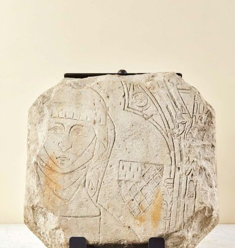 Fragment of a limestone tombstone with engraved decoration of a woman's bust. Al…