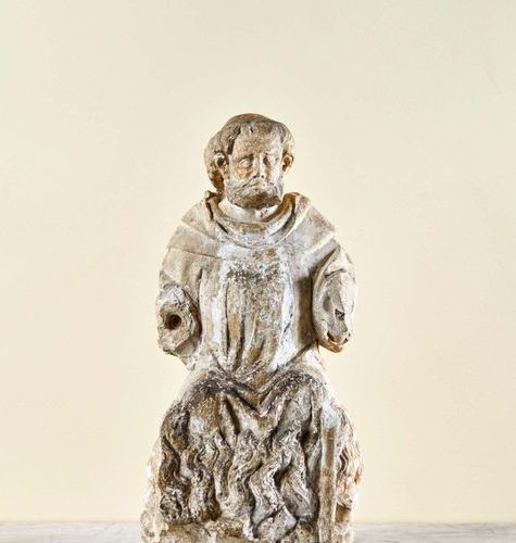 Saint Antoine in limestone carved in the round. Sitting on a fire, the holy abbo…