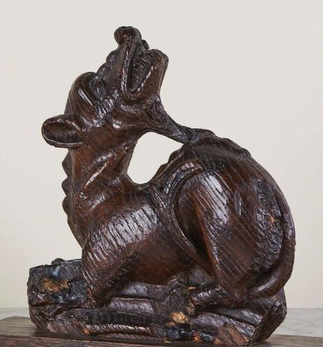 Oak stall hand rest carved in the shape of a dragon. Lying down, legs forward, t…