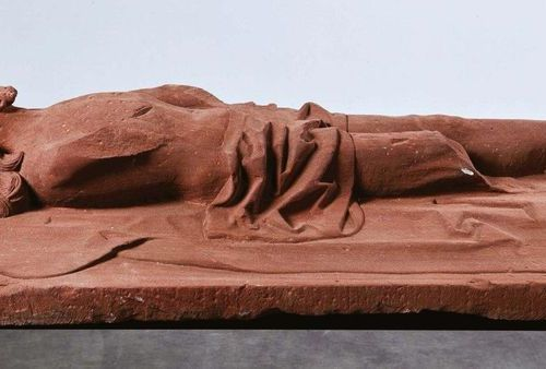 Christ lying in pink sandstone carved in high relief. He is lying on the shroud,…