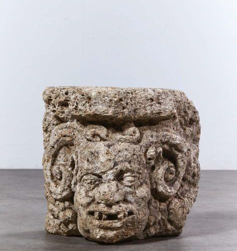 Deeply carved limestone corner capital representing a head of a grimacing satyr …