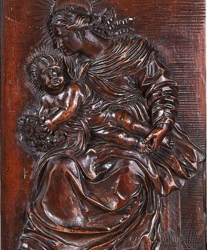 Virgin and Child in fruit wood carved in high relief. The seated Virgin is looki…