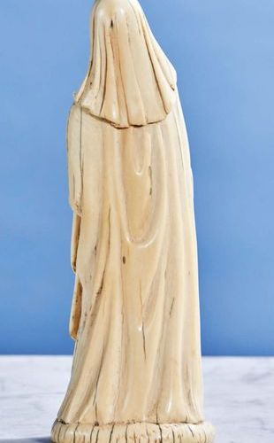 Religious saint in ivory carved in the round. Standing, she holds a closed book …