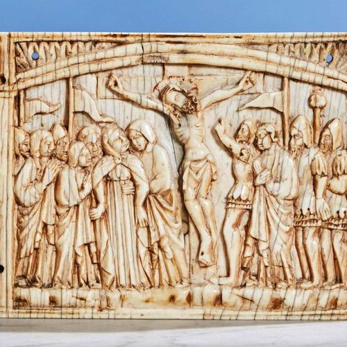 Central plaque of a carved ivory triptych representing the Crucifixion with red …