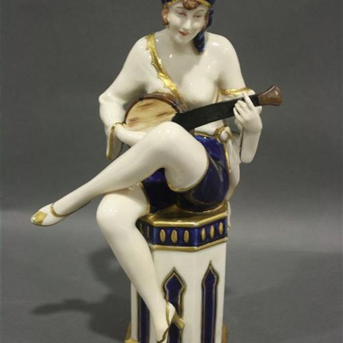 Royal Dux  Polychrome porcelain statuette with a woman sitting with a banjo. Sig…