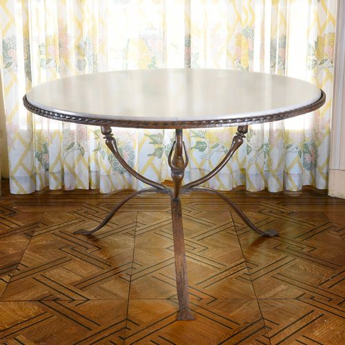 40'S WORK  Round table with a patinated wrought iron base and three curved legs …