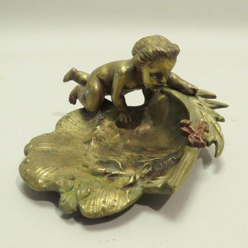 Ashtray in gilt bronze with a putto on a stylized shell. 7 x 11,5 cm.