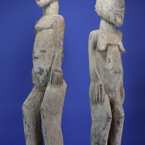 Important couple de statues, les têtes ovoïdes enserrant des petits visages aux …