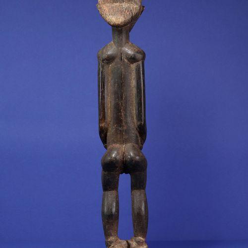 Belle statue longiligne figurant un personnage féminin debout, les bras le long …