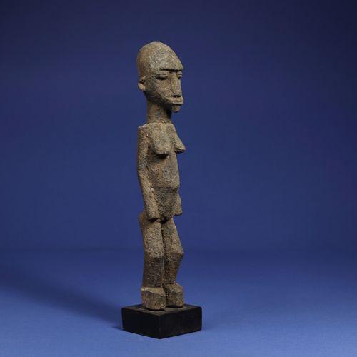 Statuette représentant un personnage féminin debout. Bois à patine croûteuse. Lo…