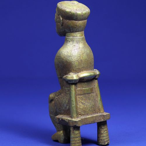 Statuette représentant un personnage assis sur une chaise, habillé à l'européenn…