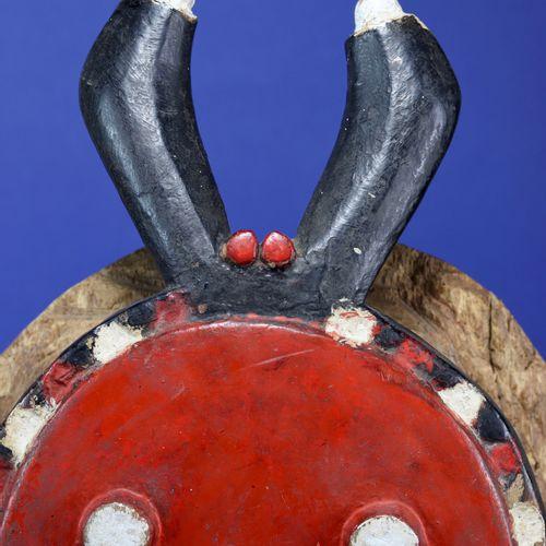 Masque kplé kplé du goli à la face ronde caractéristique, surmontée d'une paire …