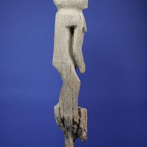 Poteau représentant un personnage féminin debout traité en quelques volumes simp…