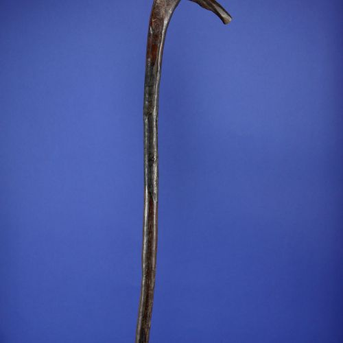 Canne au sommet de laquelle est figuré un personnage janus. Bois, patine d'usage…