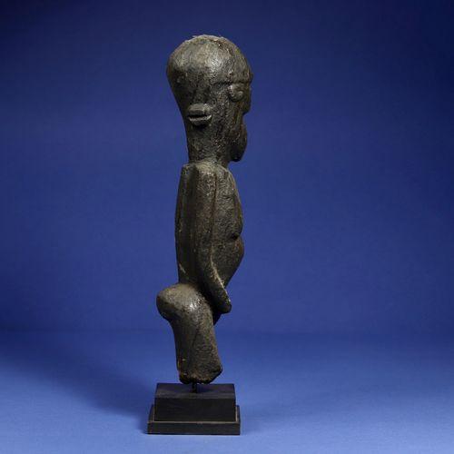 Statue féminine figurée debout, les bras collés au buste, la tête ovoïde. Bois à…
