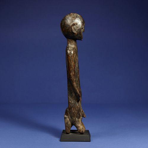 Statuette masculine assise sur un tabouret, les jambes se confondant avec les pi…