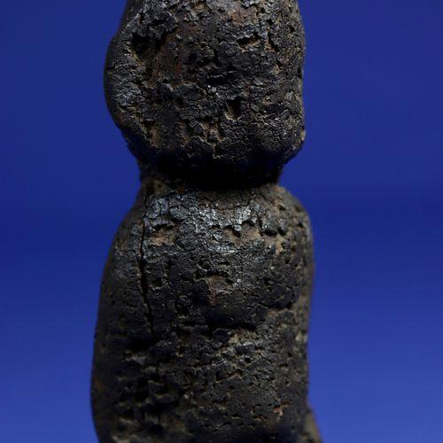 Statuette de divination, les détails de la sculpture disparaissant sous une épai…