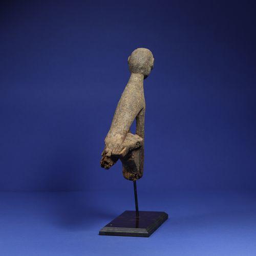 Sommet de bâton de divination figurant un personnage assis, bras rejoignant les …