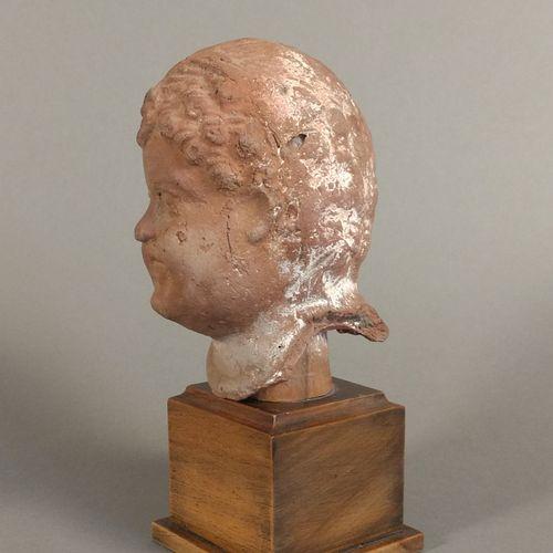 Tête ex voto représentant un enfant dont la coiffure est tressée au milieu du cr…