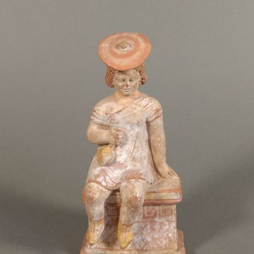 Enfant assis sur une stèle et tenant une bourse et coiffé d un pétase.  Terre cu…