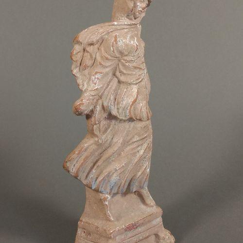 Figurine péplophore dansant sur une base à quatre pattes de lion.  Terre cuite o…