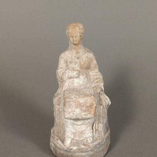 Figurine péplophore assise, tenant sur ses genoux un coffre ouvert.  Terre cuite…