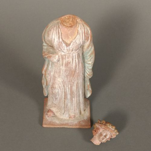 Figurine péplophore portant un manteau sur les épaules. Elle est couronnée.  Ter…