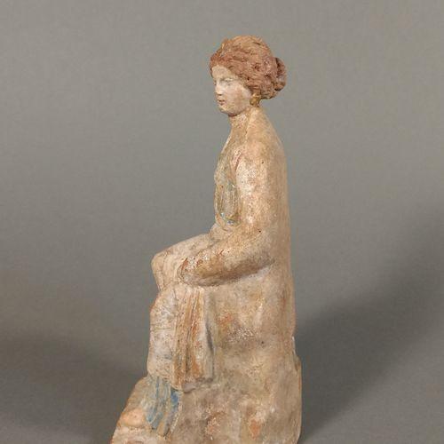 Figurine péplophore assise.  Terre cuite ocre, engobe blanc et pigments bleu et …