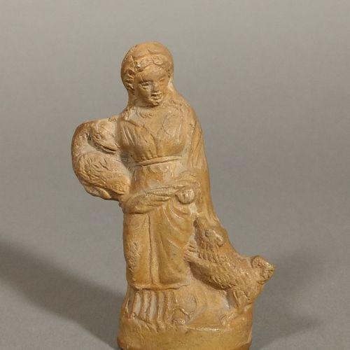 Statuette représentant une femme debout, la robe serrée à la taille. Elle tient …