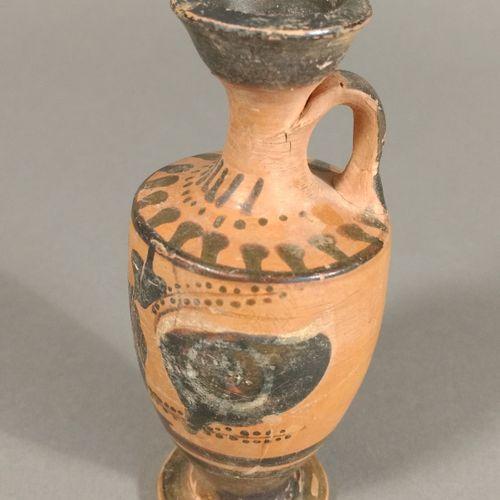 Lécythe à figure noire représentant Dionysos assis entre une paire d yeux.  Terr…