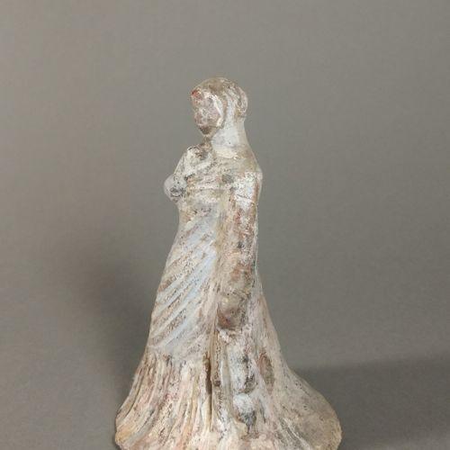 Figurine péplophore enveloppée dans un long manteau.  Terre cuite ocre à engobe …