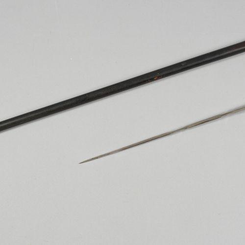 CANNE A SYSTEME Canne dague à lame biseautée, en bois noirci présentant un bouto…