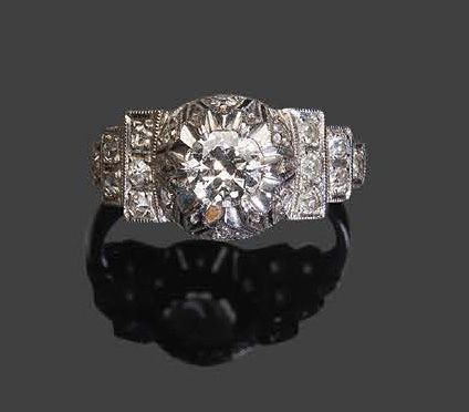 White gold ring set with a round facetted diamond in a geometrical frame of bril…