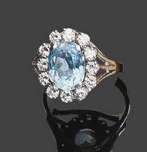 White gold ring set with an aquamarine in a circle of round faceted diamonds Pb:…