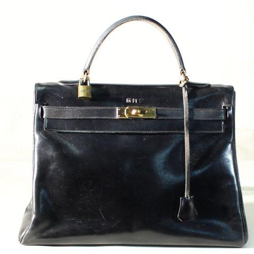 Hermès Paris. Sac Kelly en cuir noir. Porte un monogramme (une lettre manquante)…